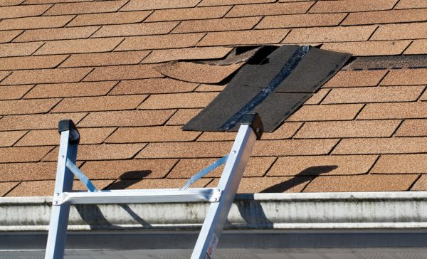 Fixing damaged roof shingles.  A section was blown off after a storm with high winds causing a potential leak.